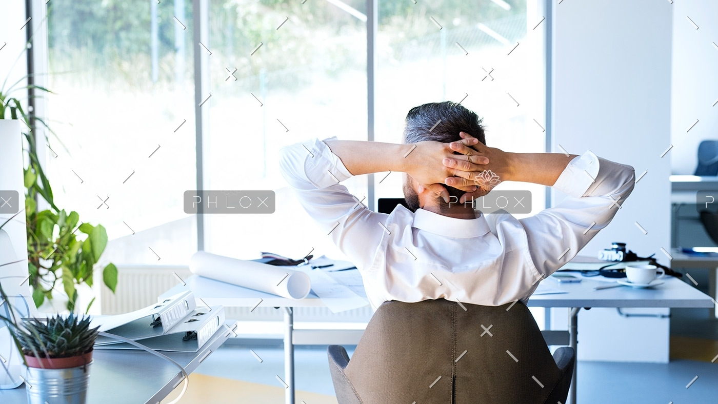 Businessman-at-the-desk-in-his-office-resting.